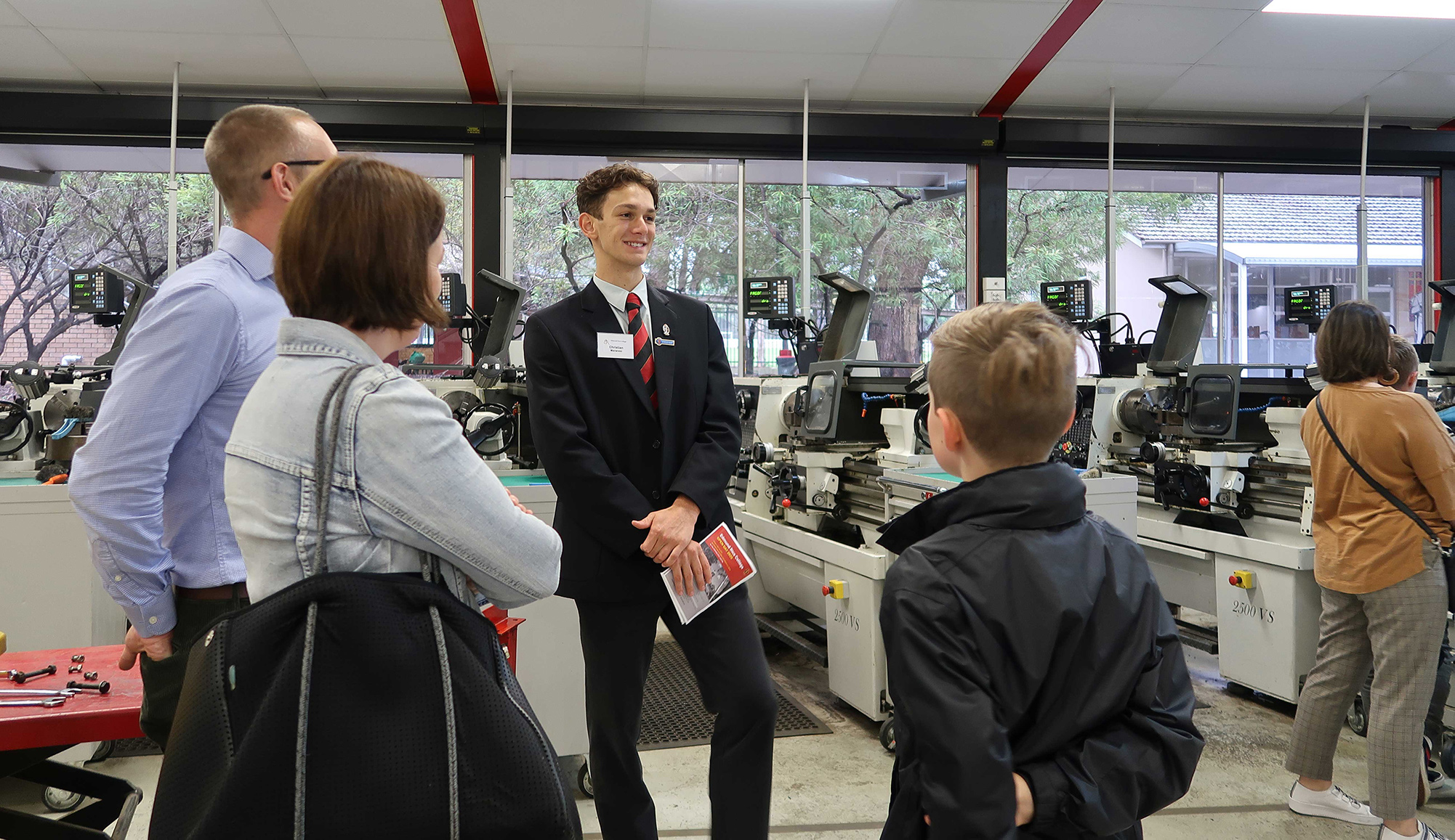 A student leads an open day tour with machinery in the background