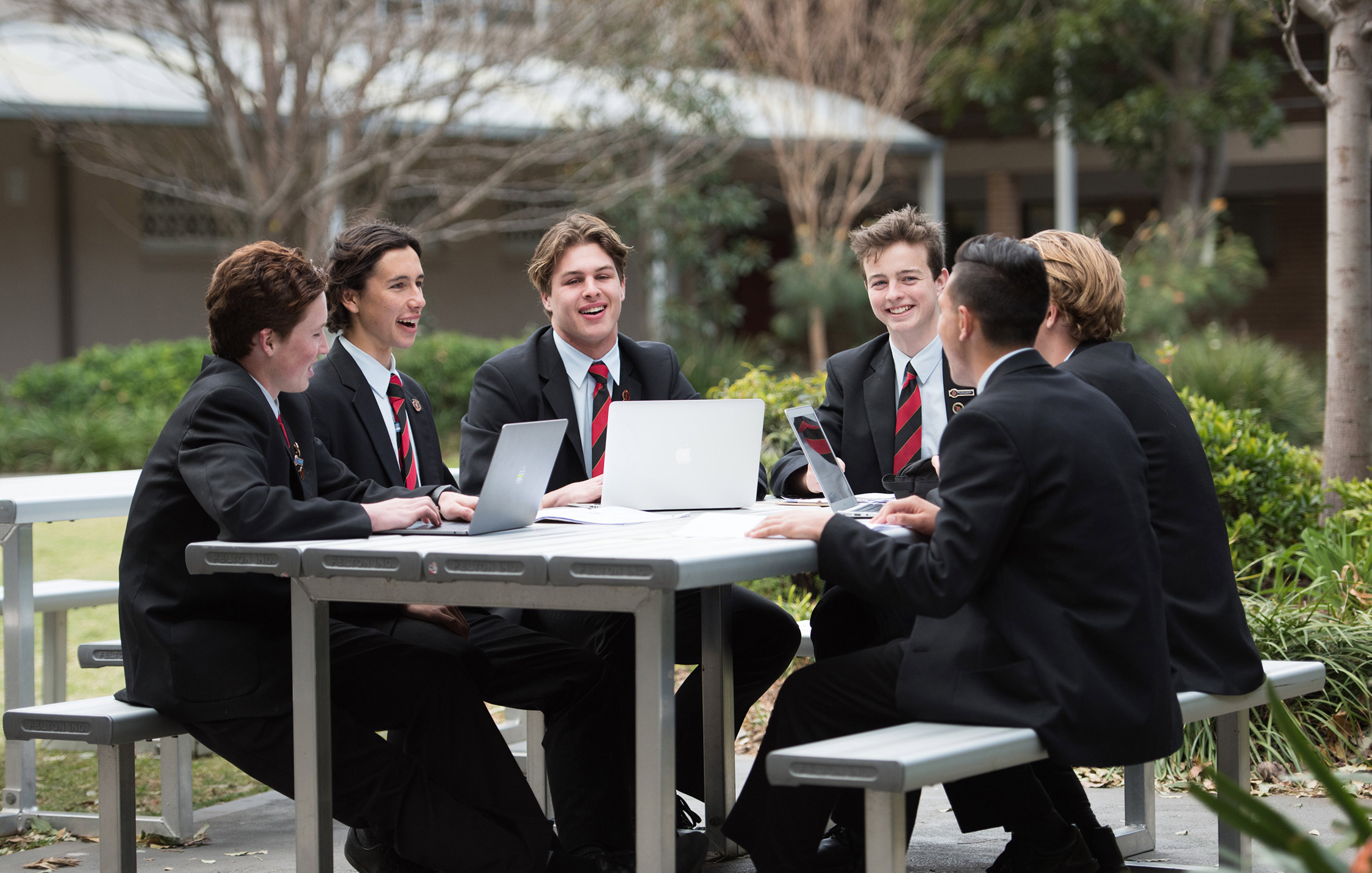 A group of students laugh together as they work on their laptops at an outdoor table