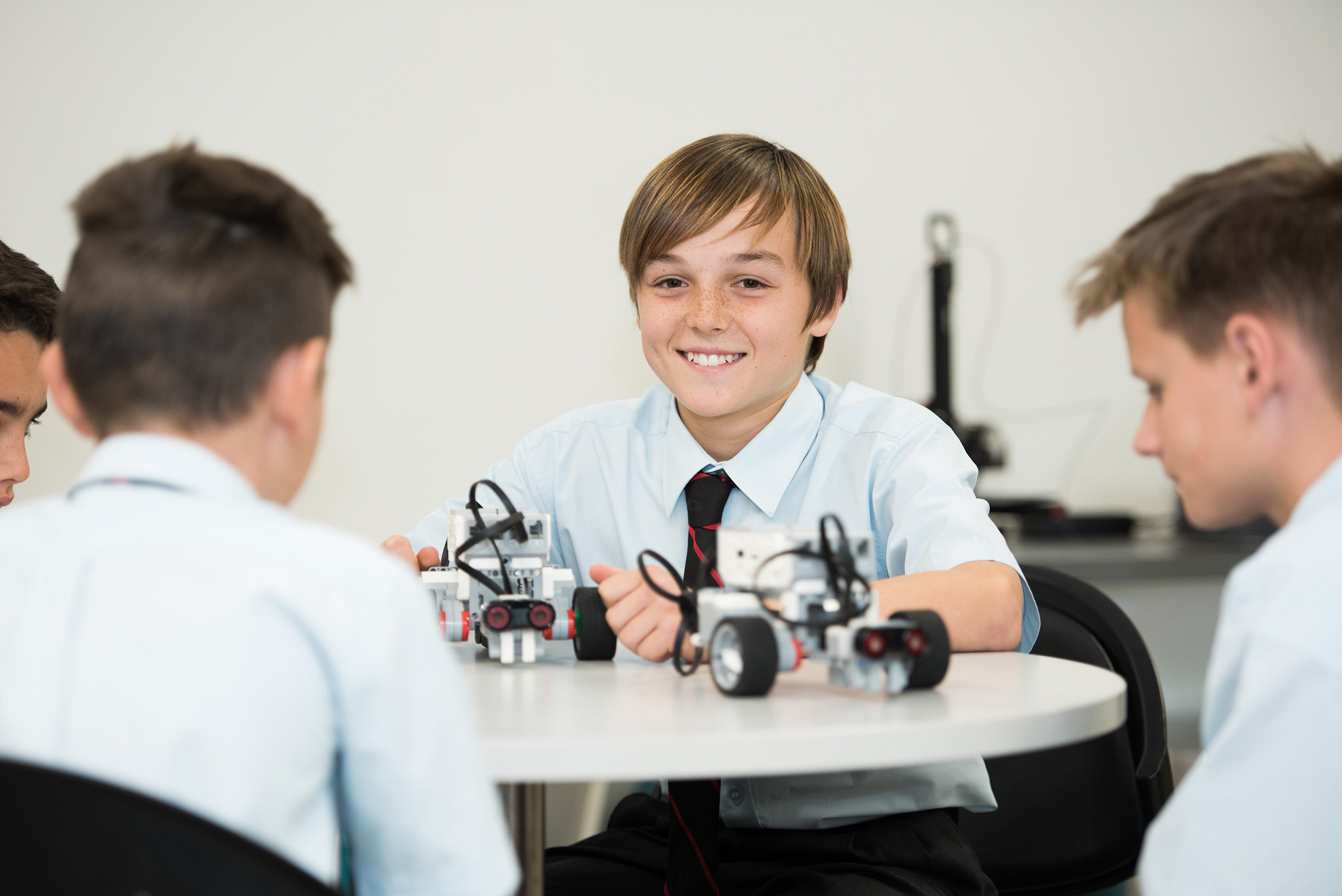 A student smiles at the camera while working on a robotics project with others