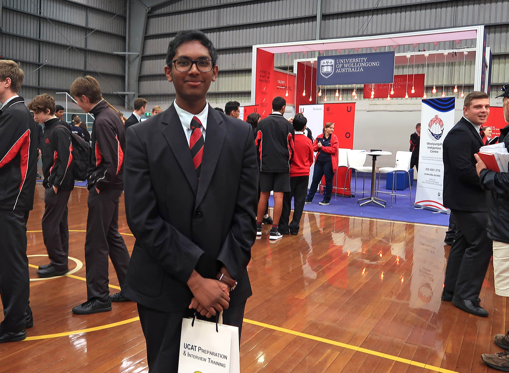 A student smiles at a careers expo while other students mingle in the background